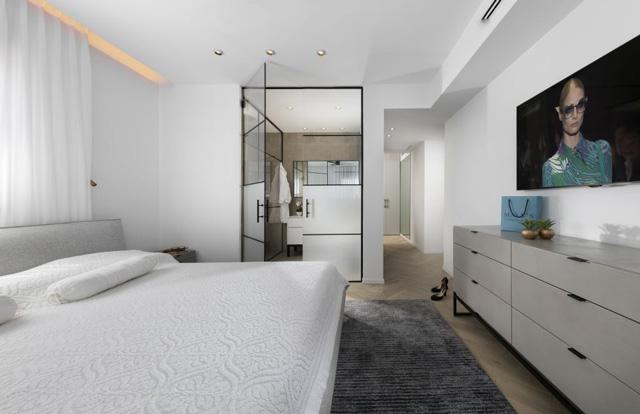 חדר שינה אלגנטי בצבעוניות רכה, קיר מדיה שמסתיר הרבה מערכות, תכנון ועיצוב של המעצבת ענבל ברקוביץ, צלם: אלעד גונן